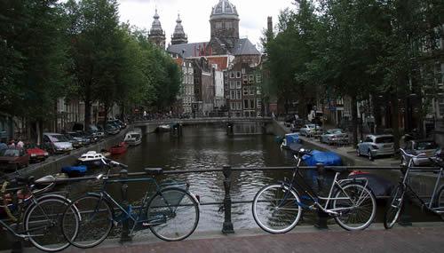 Amsterdam, biciclette parcheggiate lundo il corrimano di un ponte su un canale: la mobilità sostenibile è una delle chiavi per sconfiggere l'inquinamento (Foto cc: Joshua Doubek / Wikipedia)