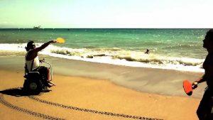 Paolo Badano che gioca a tennis sulla spiaggia: lasciando libere le mani, la carrozzina Genny consente ai disabili di praticare svariati sport
