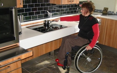 Persona in sedia a rotelle che utilizza una cucina adattata