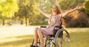 Donna bionda in sedia a rotelle con un sorriso che fa pensare ad una buona fiducia in se stessa