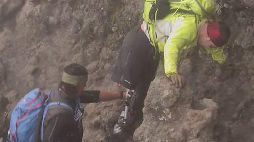 Tim Medvetz che aiuta Julian Torres a scalare uno dei punti più difficili del monte